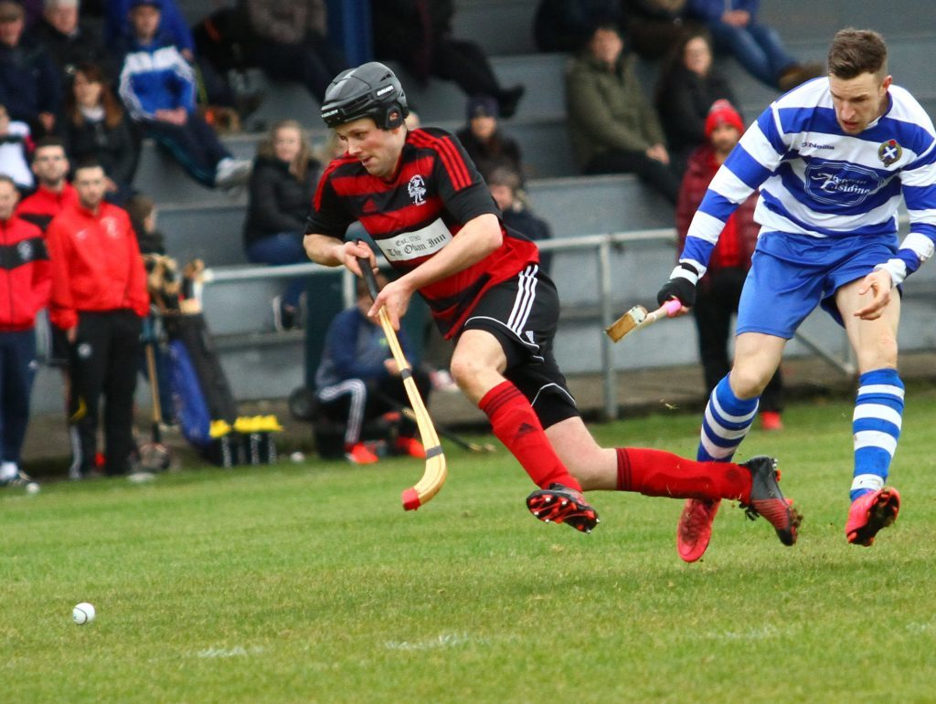 Opening goal scorer Andrew 'Papa' MacCuish is stopped in his tracks by Newtonmore's Andy MacKintosh. Champions Newtonmore suffered their first league defeat in two years, going down 2-1 to Oban Camanachd. Photograph: Kevin McGlynn.