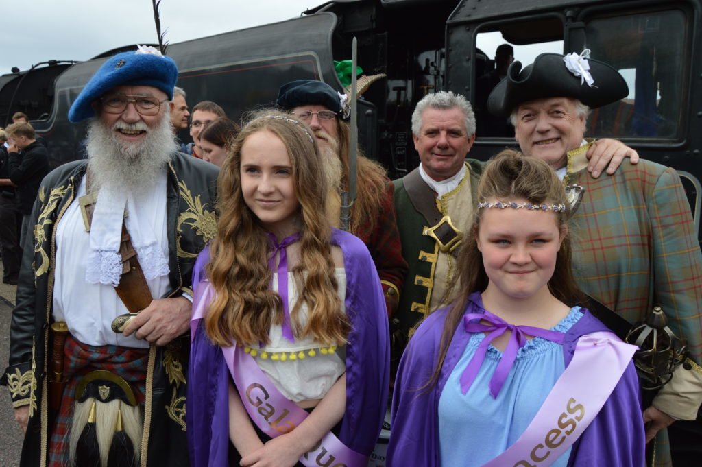 ​Gala queen and princess Megan and Laila meet Na Fir Dileas, the loyal men, who travelled to Mallaig on the Jacobite steam train collecting for the charities.