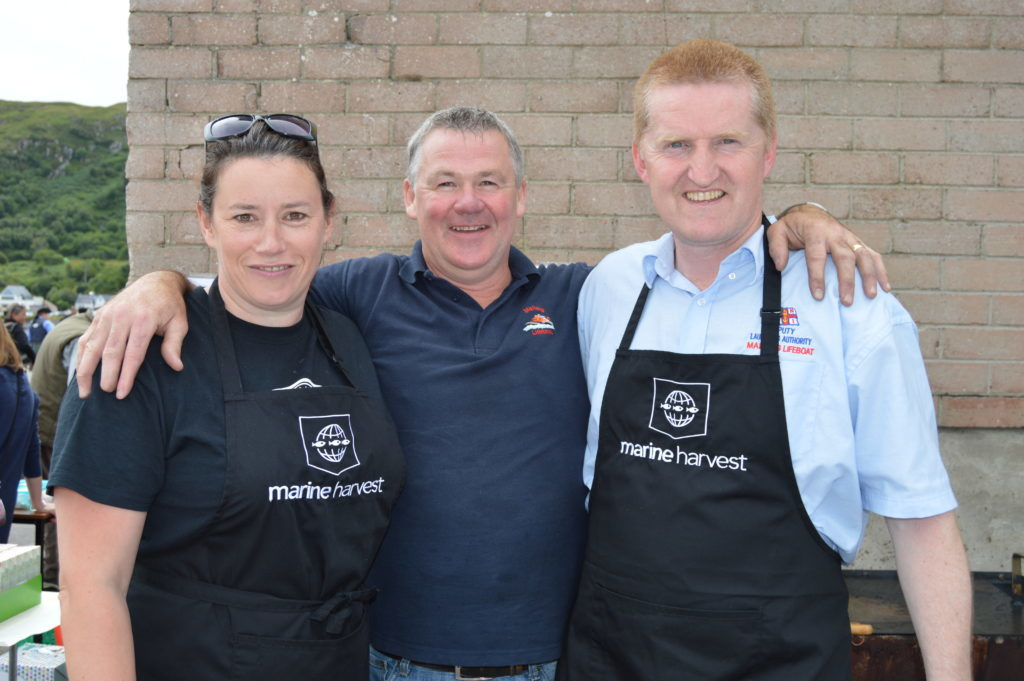 ​The Marine Harvest barbecue is always popular with the crowd. Clare Whitton, Simon MacDonald, Marine Harvest's assistant manager at Carradale and Innes Morrison from the lifeboat crew were hard at work all day. Photograph: Joanne Simms