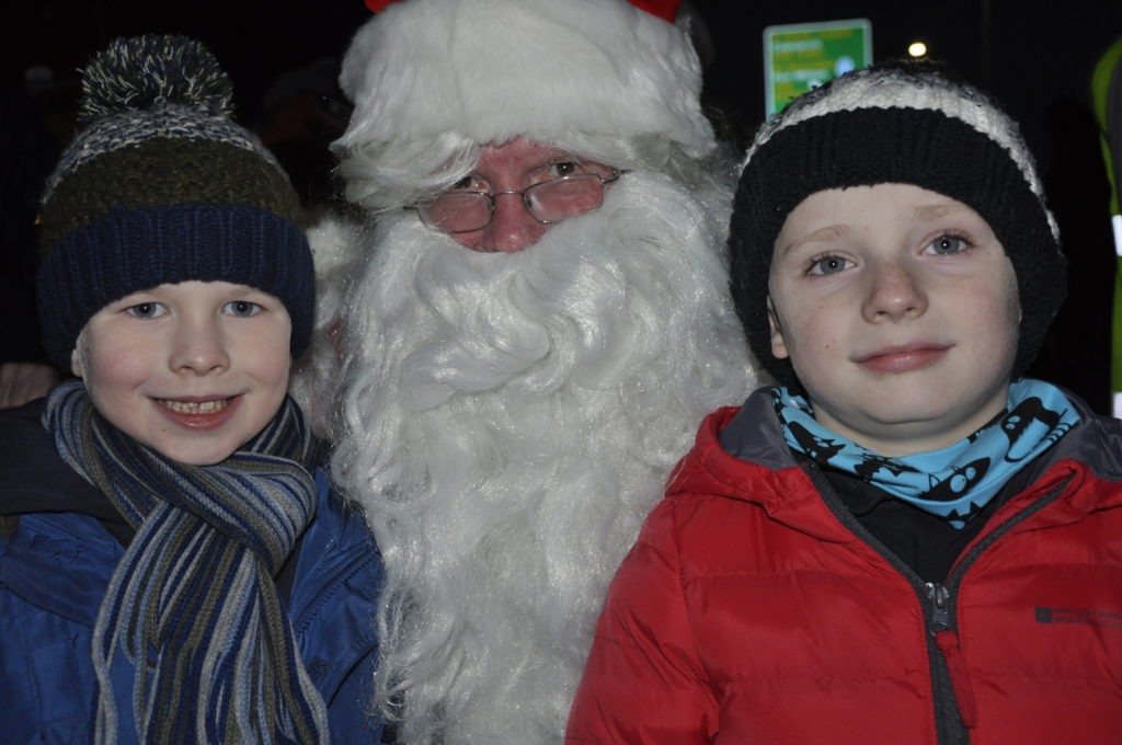 Santa with Rotary Christmas card competition winners Alexander Maxwell and Nathan Isaac, both six.