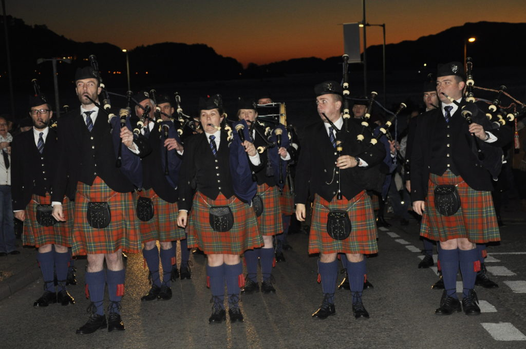 Oban Pipe Band against sunset during the reindeer parade.