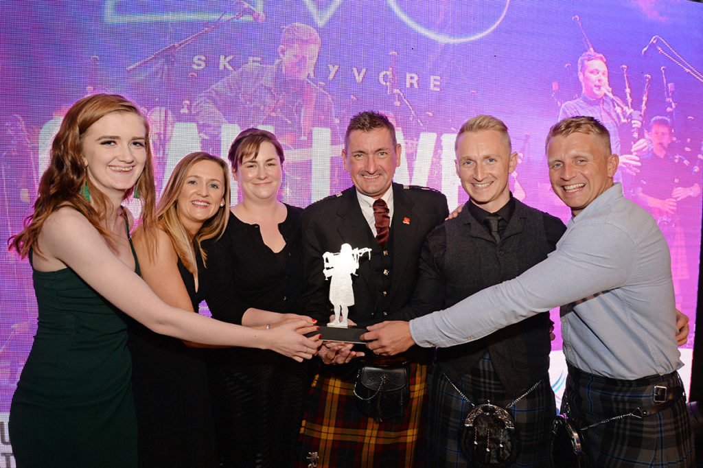 Graeme Bell, Inverness Airport general manager, Highlands and Islands Airport Limited, presents the prize for Best Cultural Event or Festival to Naomi Hoolahan, Pauline Clifford, Shannon Watson, Martin Gillespie and Daniel Gillespie, from Oban Live.