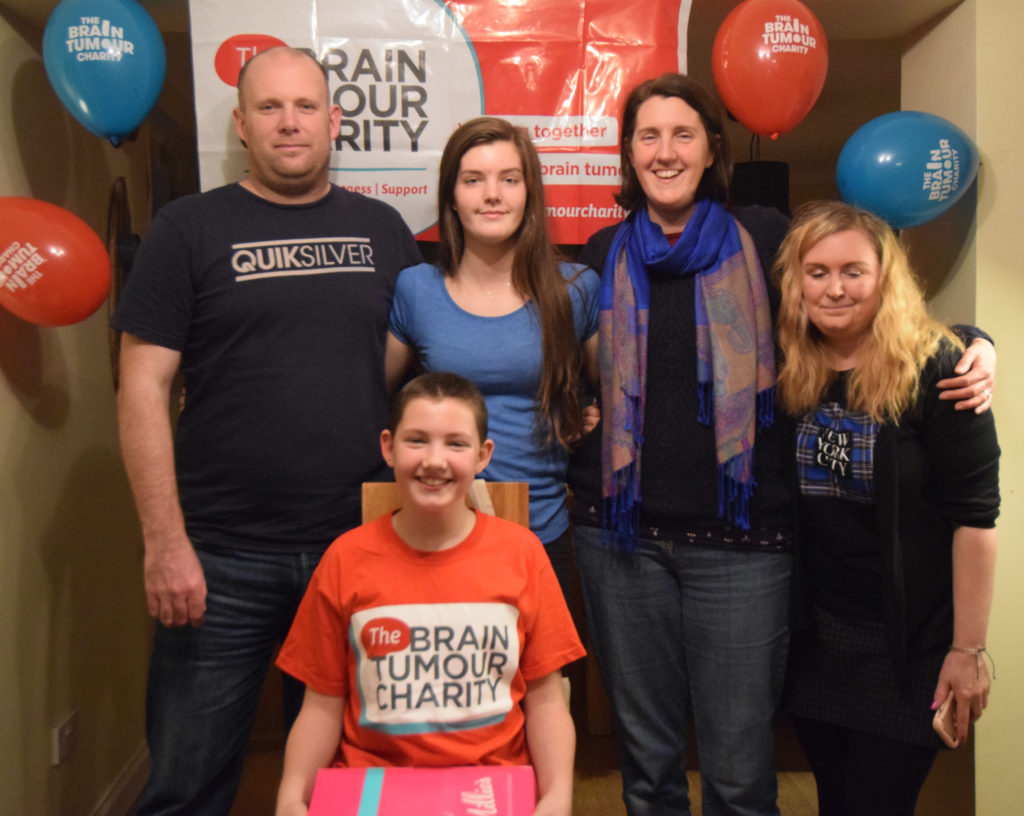 Katie with her family - back row from left dad Ally, sister Rebekah, mum Jess and Katie Grier of the Brain Tumour Charity.   NO F49 Katie family