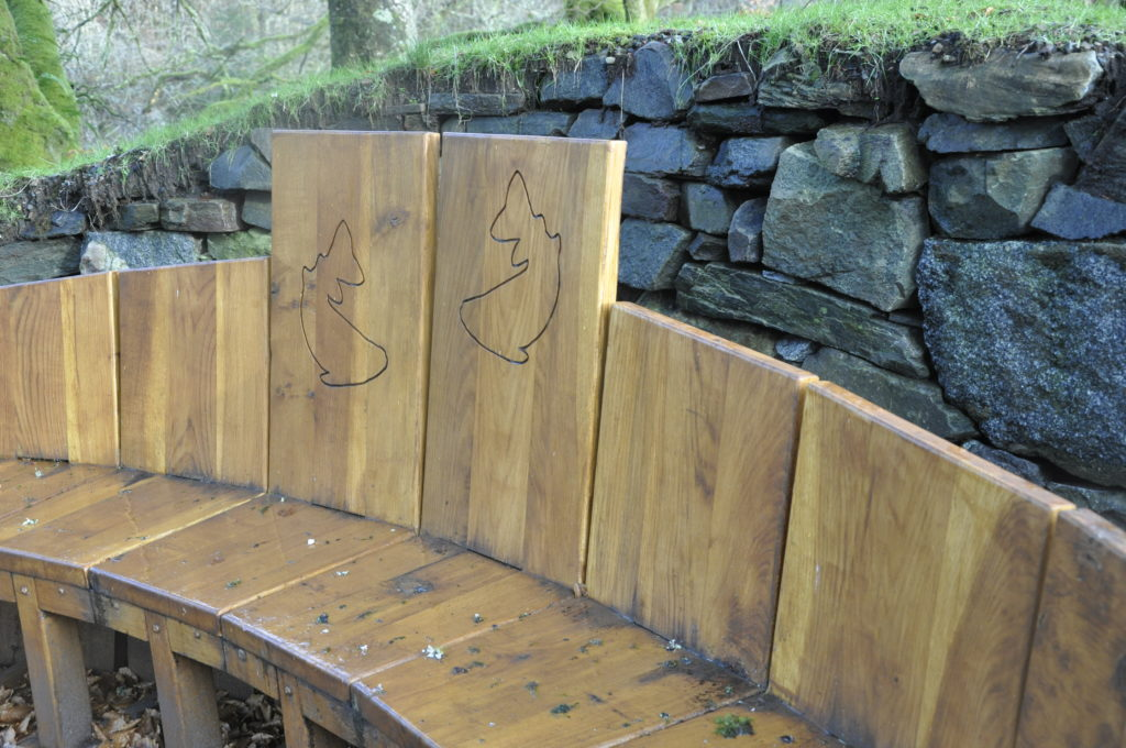 The bench was made by Ian McAdam from Eredine and local stone was used to build the wall by West of Scotland Drystone Walling Association.