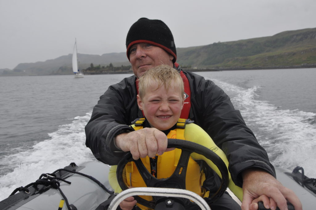 Andy Lockwood gets Fergus Hunt, six, in the driving seat of a rib boat.