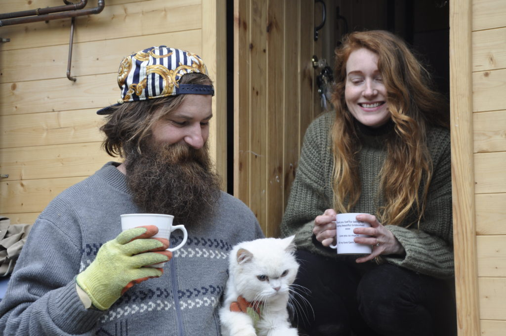 Simon Hunt and his wife Stef Burgon with their rescue cat Frank, taking a break.