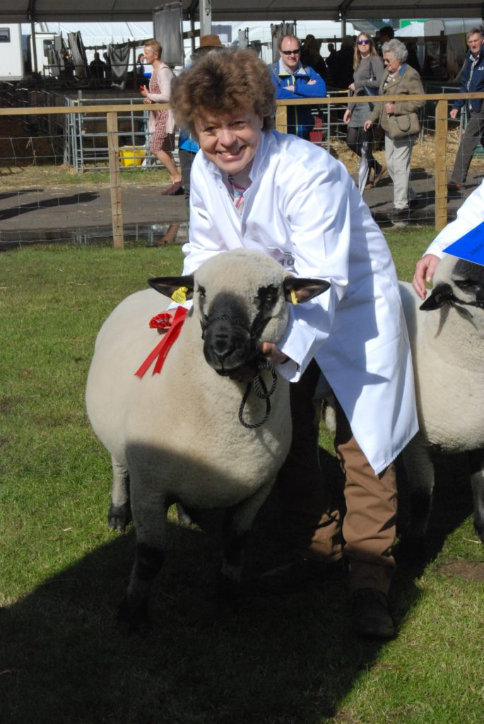 A delighted Janet Hill is handed the first prize rosette for her shearling ram. 06_a26RHS03_HillHampsDown