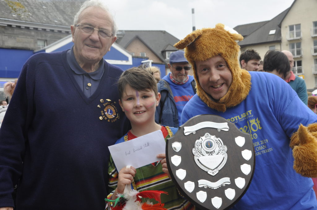 Oban and Lorn Lions Club president David Coates presents the best-dressed stall shield to Spotlight  Musical Theatre Group's Lachie D'Arcy and Stephen Day. 16-T23_charitiesday15-bestdressedstall