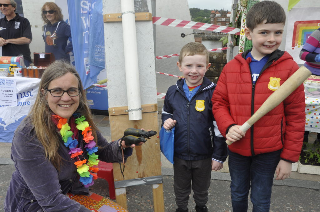 New Hope's Catriona Petit mans the splat-a-rat stall while cousins Ayden Campbell, 8, and Charlie Shaw, 4, wait to have a go.