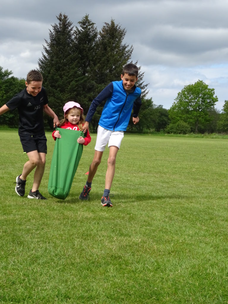 This youngster receives a helping hand in the sack race.
