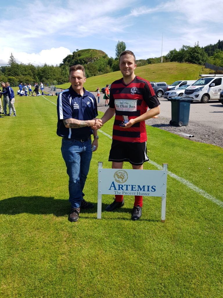 Les Kinvig of the Macaulay Association hands over the South man of the match award to Oban Camanachd's Andrew 'Papa' MacCuish.