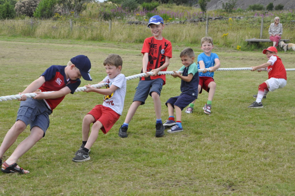 Heave ho - the boys do their best at tug of war against the girls.