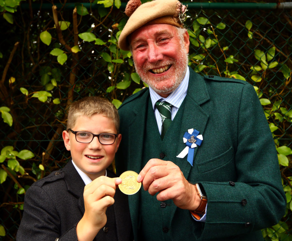Archie Johnston from Bunessan on Mull receives the Duke of Argyll's gold medal from piping steward Torquil Telfer.