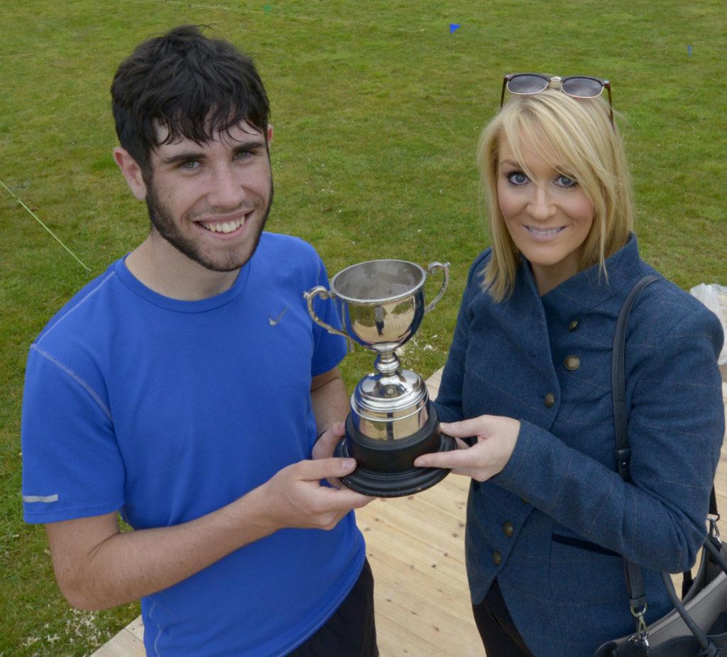 Games Chieftain, Kirsteen MacDonald presents the running trophy to Louis MacDonald from Morar.  Photograph: Iain Ferguson, alba.photos