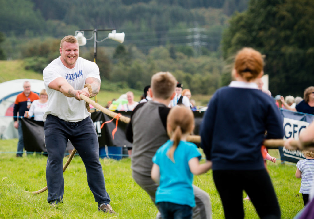 Strongman legend Tom Stoltman takes on local children in a tug-o-war.  NO F35 LAS 2019 - - Scotlands stronget man - Tom Stoltman 02  NO F35 LAS 2019 - - Scotlands stronget man - Tom Stoltman 02