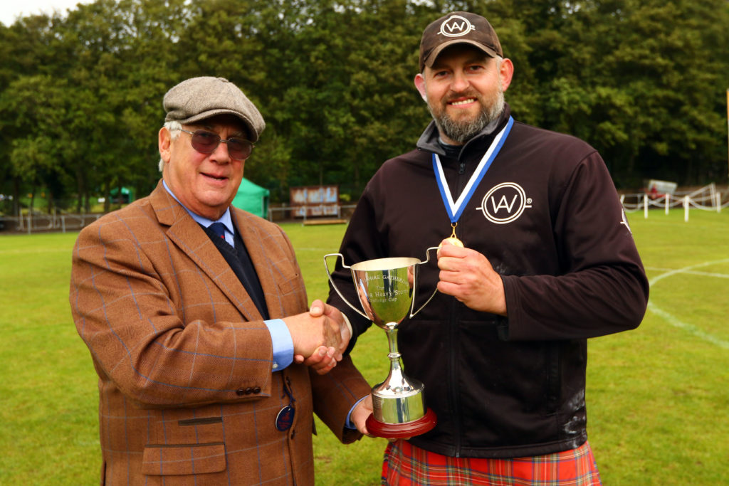 Richard Campbell Walton presents the trophy for winning the caber tossing to heavy athlete Lukasz Wenta.