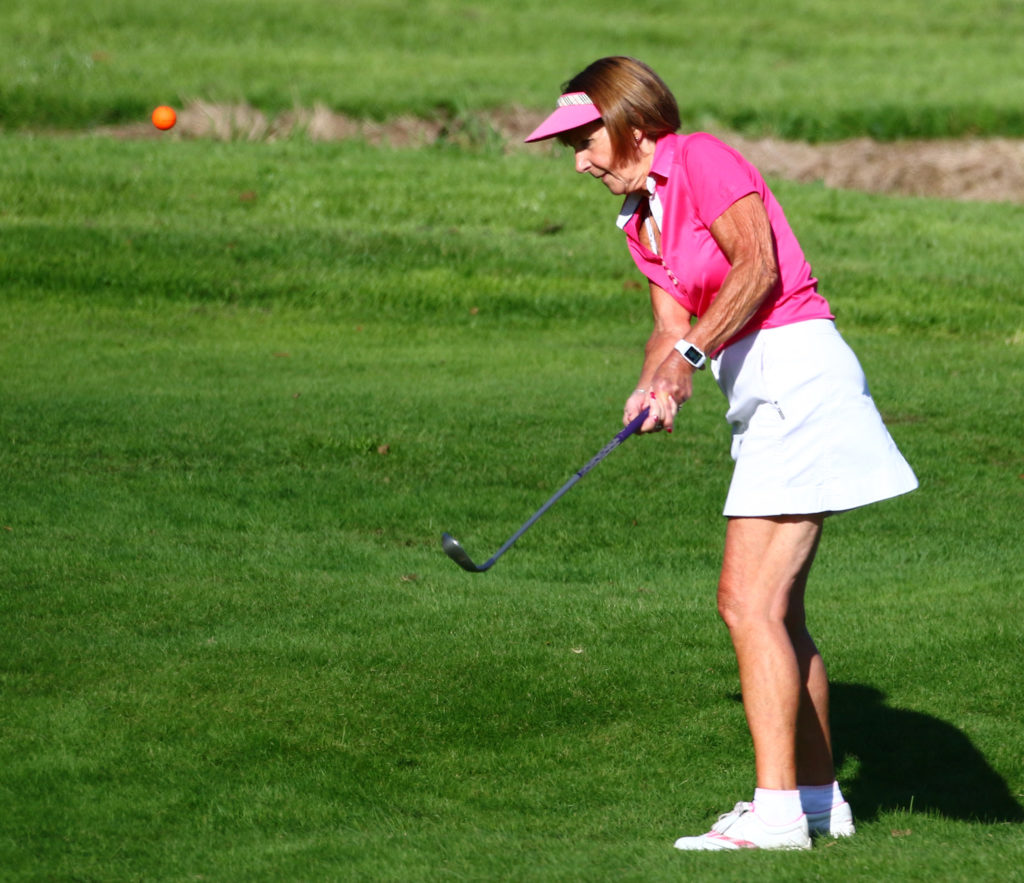 Mary Plunkett, playing for the Pink Ladies, plays her chip to the 18th green.