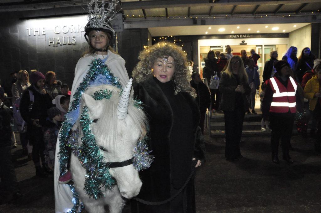 Elaine Cameron leads fairy princess Alexandria Betts on PK the unicorn at Friday Night's parade.