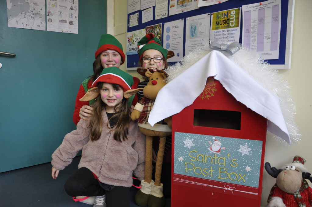 Elves Rowan Gemmell, Erin Farrely and Isabella Nicholson collect the Christmas mail at the Rockfield Centre.