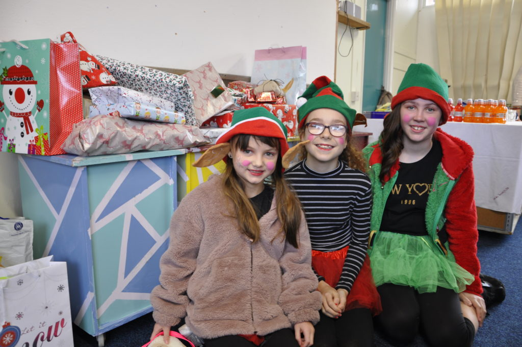 Elves Rowan Gemmell, Erin Farrely and Isabella Nicholson help with the present donations at the Rockfield Centre.