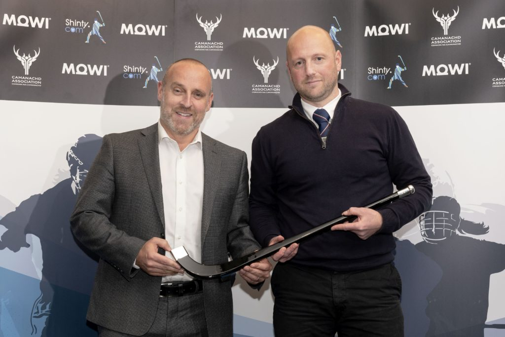 Mowi's Ian Roberts presents the Coach of the Year award to Kingussie's John Gibson.  Mowi Shinty Awards Luncheon and Conference at The Kingsmills Hotel, Inverness.