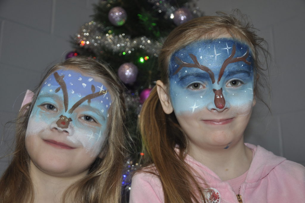 Deri France, 6, and Iona Richell, 8, with their festive faces painted.