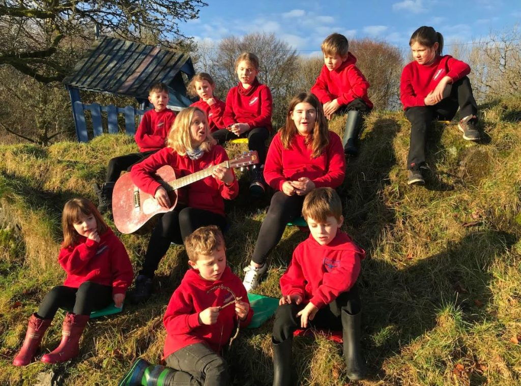 Outdoors singalong with headteacher Catherine Davies and pupils who hope their new head will be just as musical.