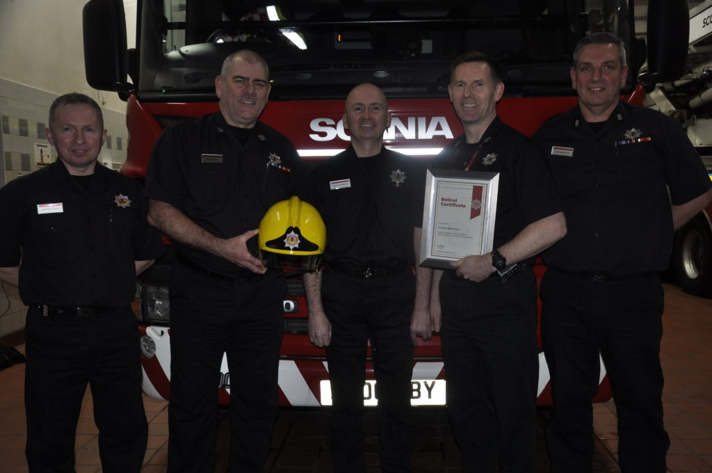 Brian MacDonald, centre, pictured receiving his retirement certificate from his brother John B MacDonald, Argyll and Bute Area Commander Paul Devlin,  Glasgow Area Commander Roddie Keith and Oban watch commander Dougie Black. 16_T04_BrianMacDonald03