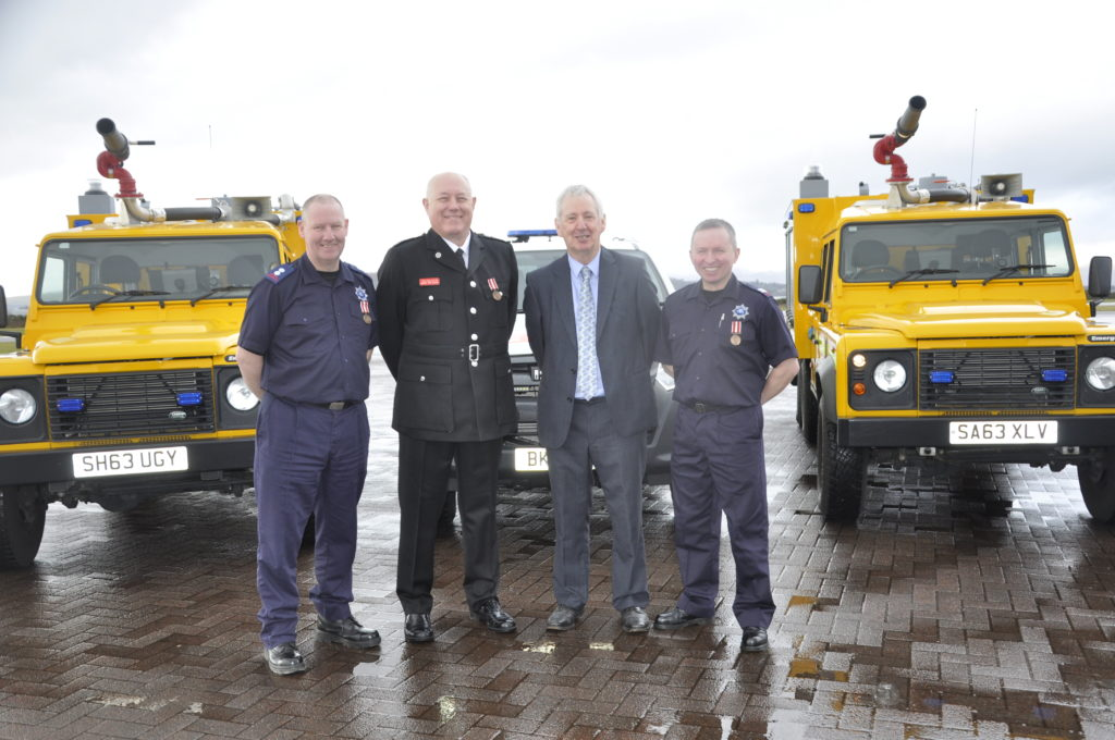 Depute Lord Lieutenant Andrew Campbell presented long-service awards to, from left, Crew Commander Murray MacGregor, Senior Airport Fire Officer Tom Eddleston and firefighter John MacDonald.