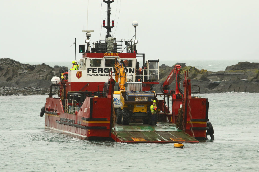 A barge brings in heavy machinery to clear the channel at Easdale harbour. Picture by Kevin McGlynn.