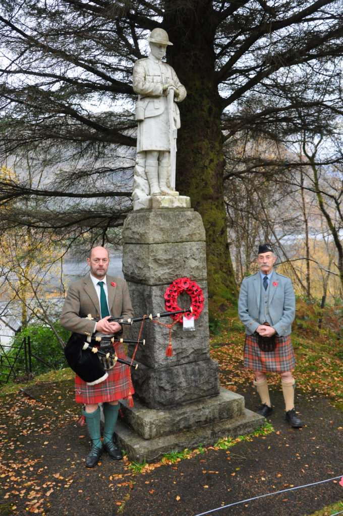 A wreath was laid at Glenfinnan war memorial on Sunday afternoon on behalf of the local community by Tearlach MacFarlane, right. His son, Iain, played the pipes. and local resident, Lt Cdr Dave Taylor RN read Binyon's famous lines.   NO F46 Glenfinnan Remembrance 01