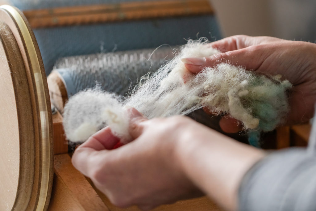 Making wool by hand with a drum carder.