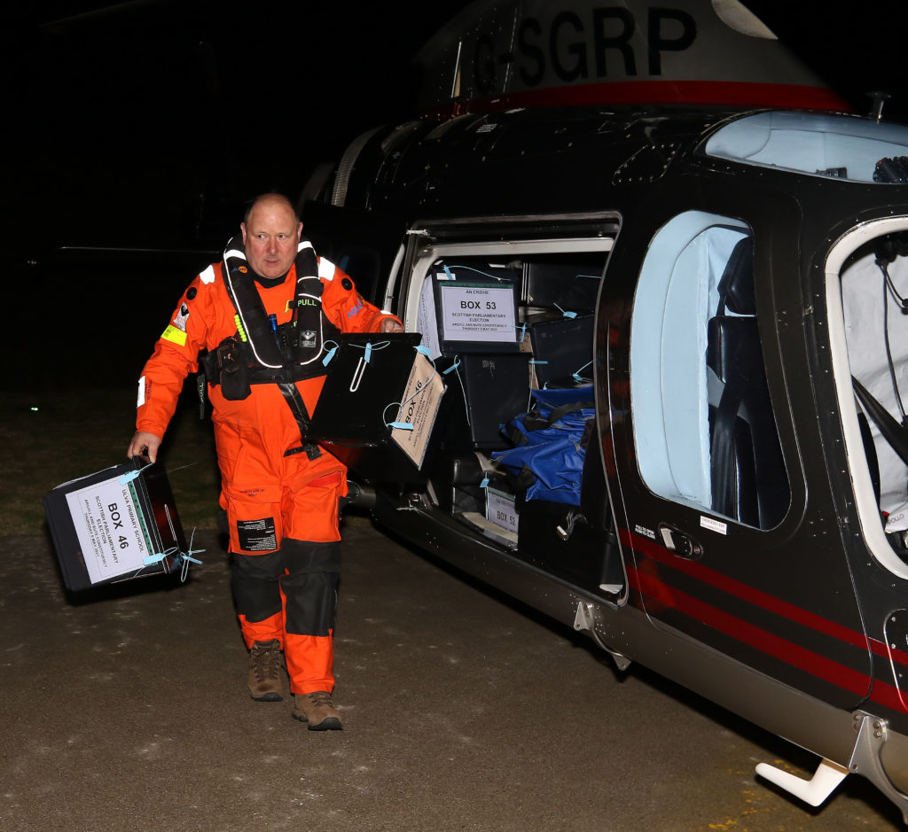 The helicopter crew helping to unload the boxes at the helipad at Mid Argyll Hospital. Photograph: Kevin McGlynn