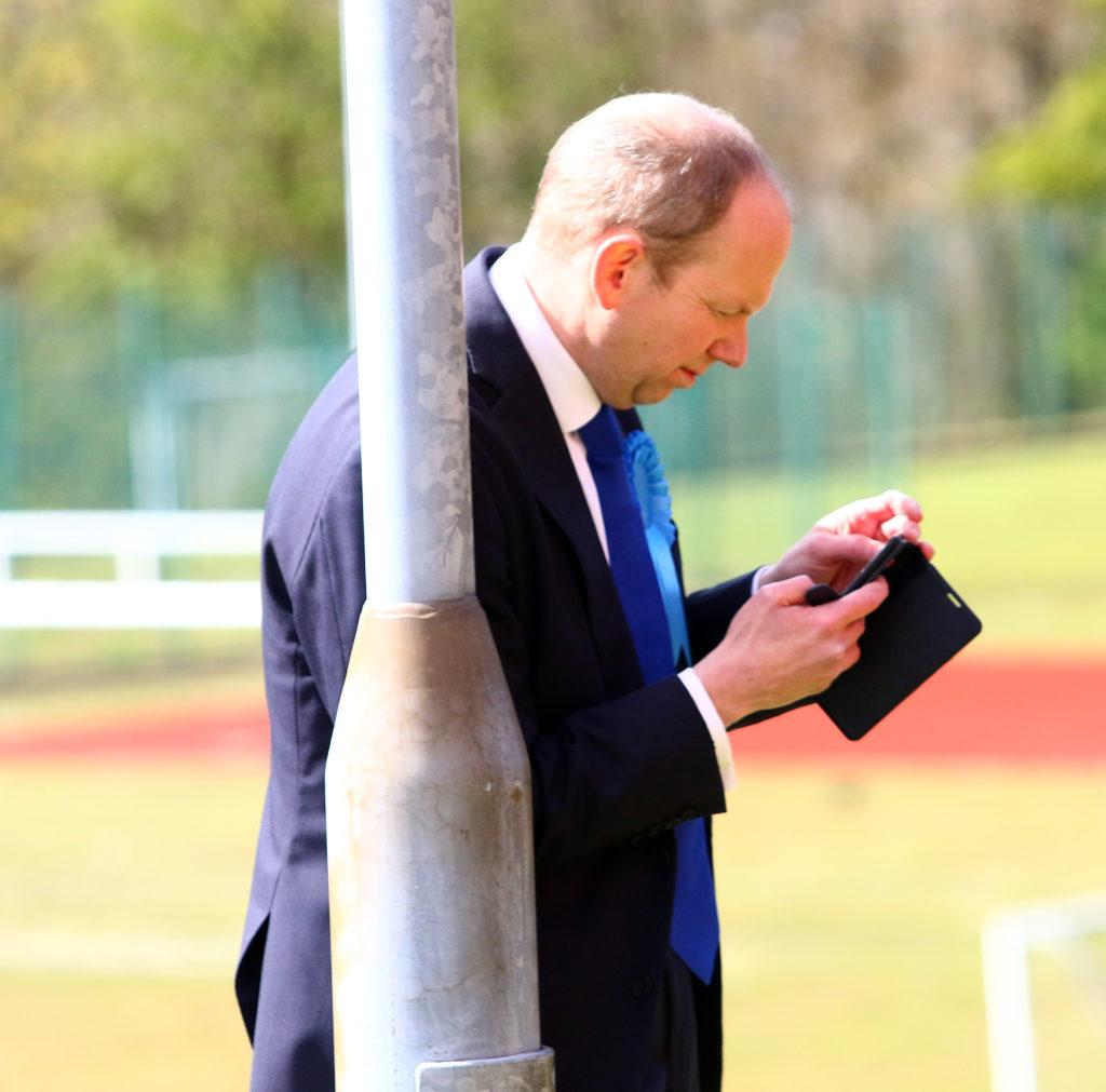 Donald Cameron checks his phone after everyone was evacuated from the count due to a false fire alarm. Photograph: Kevin McGlynn