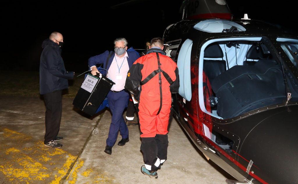 Helicopter crew with David Logan unloading the boxes at the helipad at Mid Argyll Hospital. Photograph: Kevin McGlynn