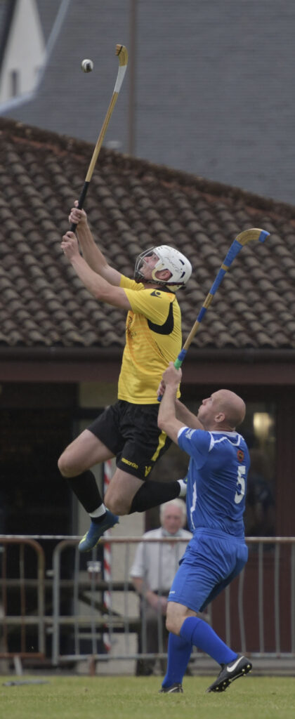 A vertical take off from Arran MacPhee as he escapes a tackle from Ryan Stewart.  Photograph: Iain Ferguson, alba.photos