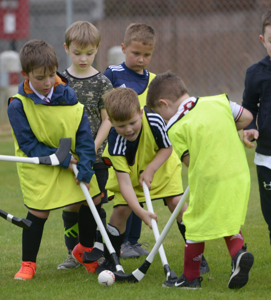 Big effort going in from these players - some more action from the street shinty. Photograph:  Iain Ferguson, alba.photos  NO-F30-Shinty-Street-League-03-scaled.jpg