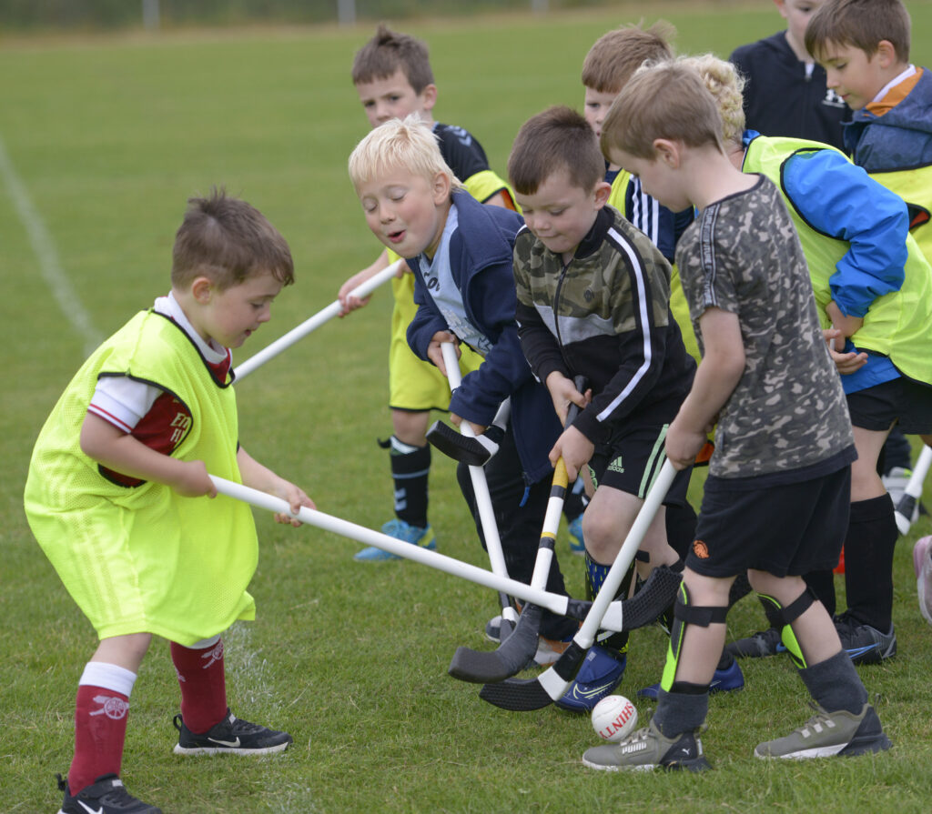 Enthusiastic youngsters try out their skills on the pitch. Photograph:  Iain Ferguson, alba.photos  NO-F30-Shinty-Street-League-05-scaled.jpg