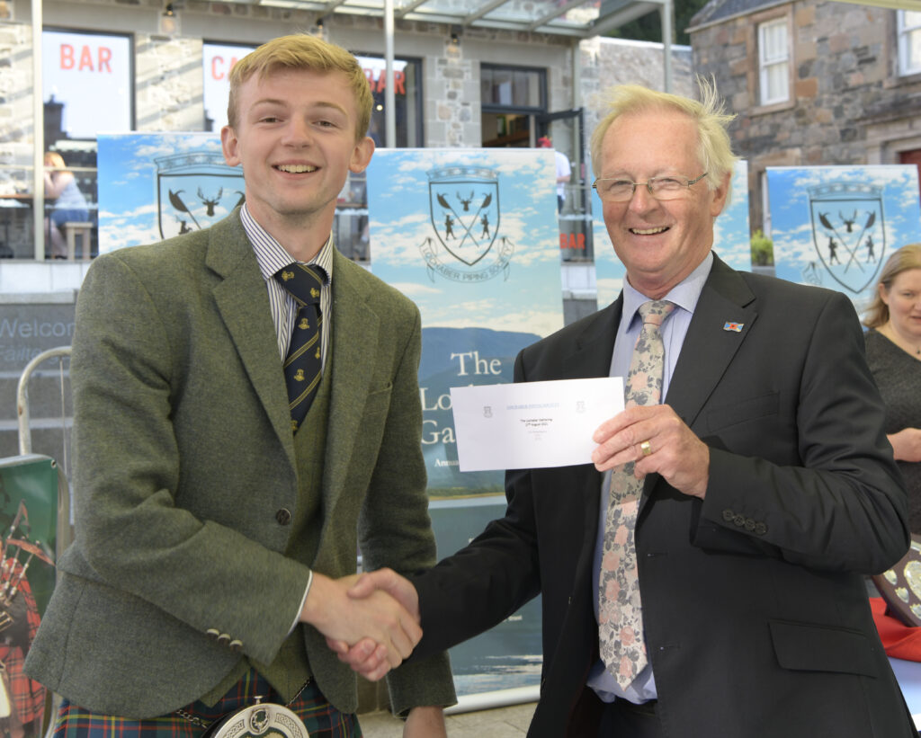 Local piper Sandy Cameron who took second place in the P/A Grade Piobaireachd,  is presented with his award by Councillor Alan Henderson. Photograph: Iain Ferguson, alba.photos  NO-F36-Lochaber-Gathering-02-scaled.jpg