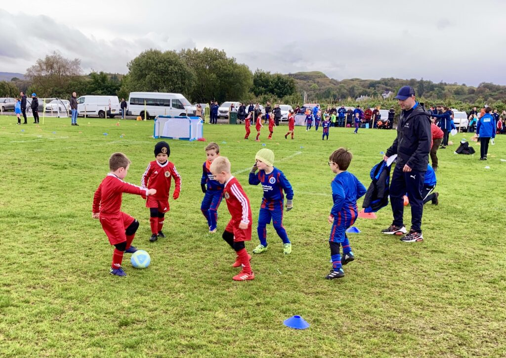 Players from Campbeltown Pupils and Lochgilphead Red Star compete for the ball.