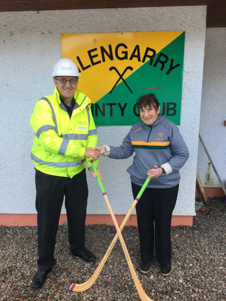 Martin MacGillvray of Morrison Construction hands over the new camans to club treasurer, Anne Davies. NO F01 Glengarry shinty