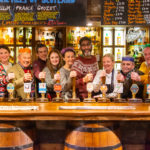Some famous faces behind the bar at the Clachaig Inn are, from left, Kenny Boyle, Natalie Clark, Frazer Hines, Alexander Teunion, Caitlin Blackwood, Karen Bartke, Sanjeev Kohli, Clare Grogan, Sylvester McCoy and Alasdair McCrone. Photograph: Magic Monkey Films. NO F04 Perfect Strangers 05