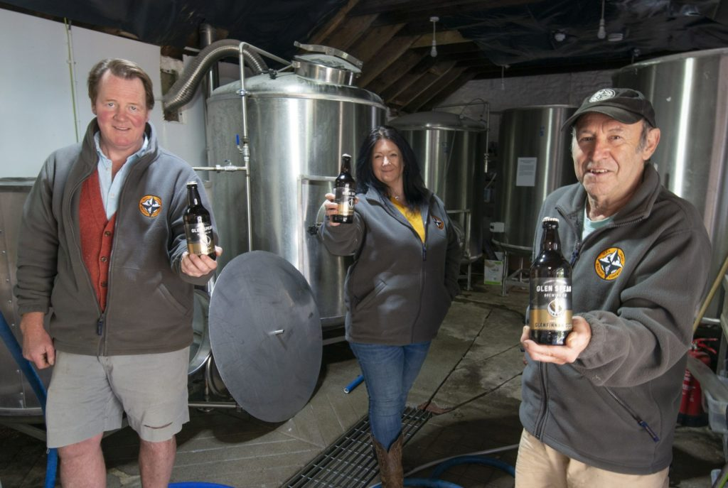 Ian- Peter MacDonald, far left, Lucy Hicks and John Fish with the new Glenfinnan Gold beer in front of equipment from the former Glenfinnan Brewery. Photograph: Iain Ferguson, alba.photos NO F29 GleanSpean Brewery 01