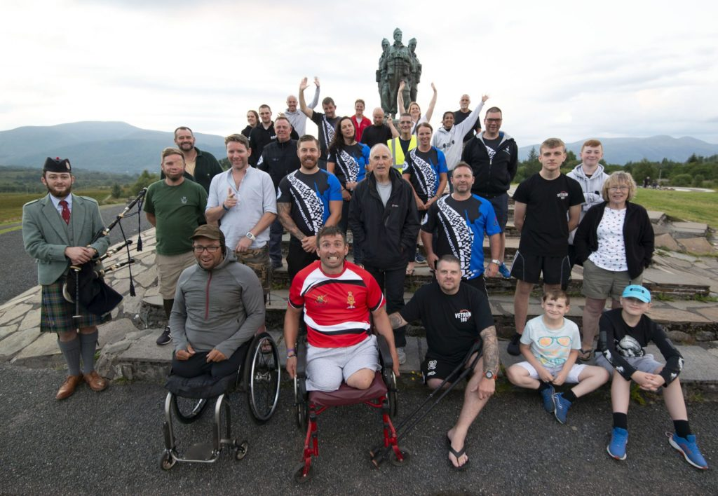 Lochaber piper Finlay Cameron, far left, played 'Flo'ers O' the Forest' for the party of injured military veterans who paused at the Commando Memorial. Photograph: Iain Ferguson, alba.photos NO F34 Veterans charity walk 01