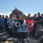 The triumphant team on the summit standing in front of Bert's peace cairn with the Black Country flag. NO F35 Bissell 02