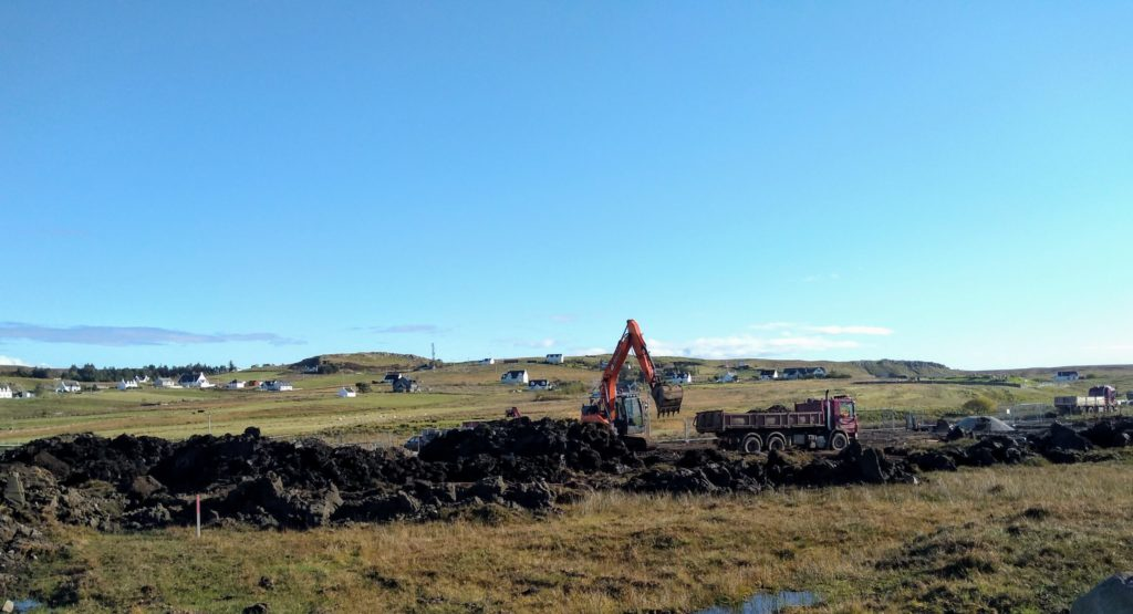Work at the site with Garafad and Clachan townships in the background. NO F47 Staffin housing