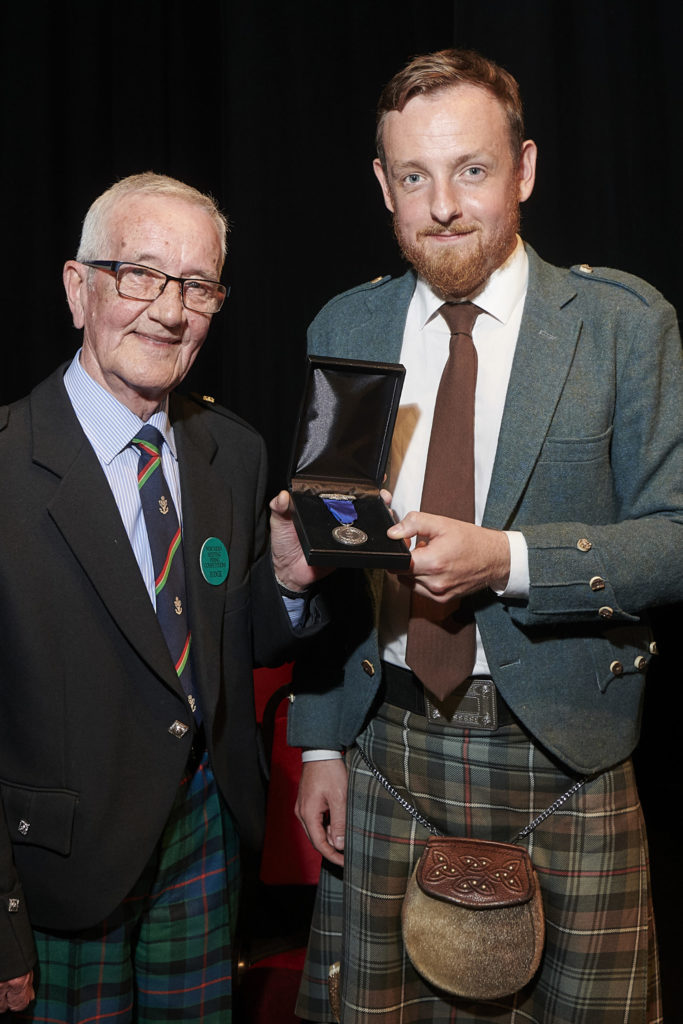 The late Pipe Major Iain Murdo Morrison (pictured left) with James Mackenzie, on the occasion of James winning the Silver Medal at the Northern Meeting in Inverness in 2019. NO-F05-PM-Morrison-James-Mackenzie-scaled.jpg