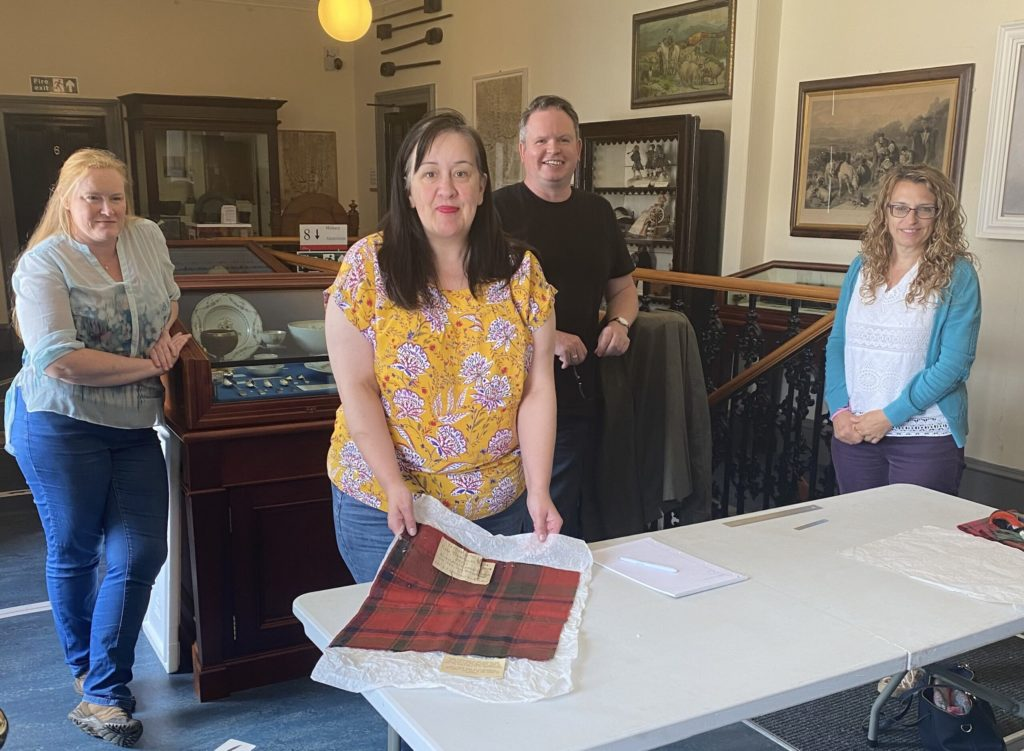 Jo Watson holds up the piece of tartan from Flora MacDonald's wedding dress, watched by Nikki Laird, far left, Robin Elliott and Vanessa Martin. Photographs: Courtesy of Joanne Watson and by permission of the West Highland Museum. NO F28 Flora tartan 03