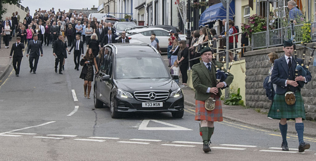 Hundreds of people lined the streets of Mallaig on Friday to bid fairwell to Lachie Robertson as the funeral procession made its way from St Columba's Church of Scotland to the harbour. The hearse paused briefly beside his boat 'Reul a' Chuain' before making the journey to Beoraid Cemetery in Morar, where a large gathering of his friends, many travelling from the islands, joined family members for the interment service by Rev Stewart Gourlie. Photograph. Iain Ferguson, alba.photos NO F29 Robertson Funeral procession