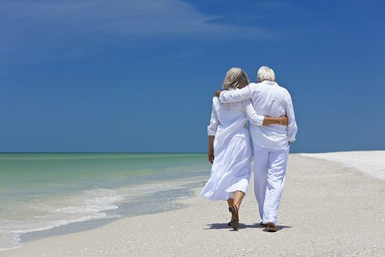 Rear view of senior couple walking on beach